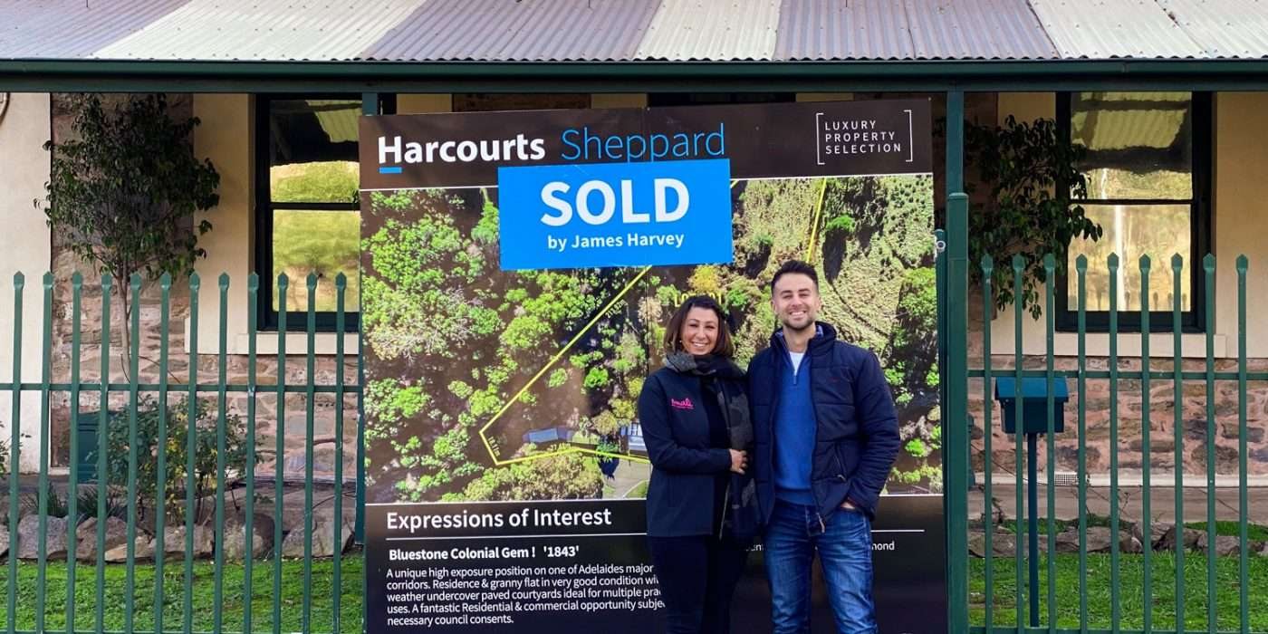 couple standing in front of sold sign with house in background