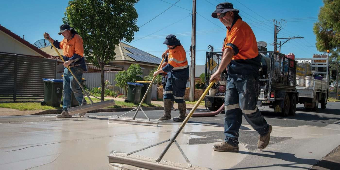 tradesmen applying CoolSeal® – a light-coloured reflective asphalt coating to a road surface